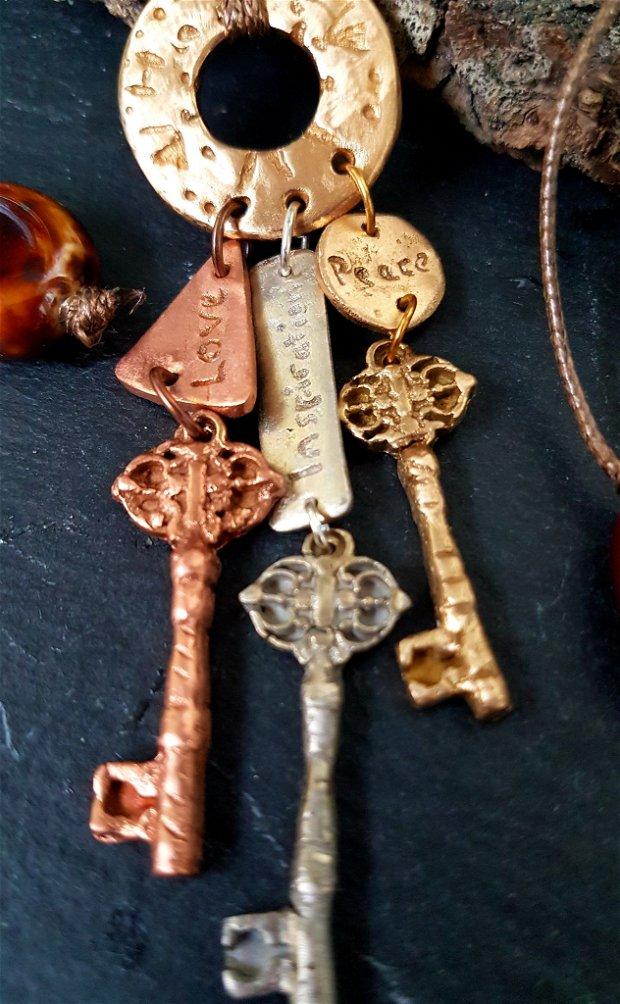 colier de autor, reglabil ca lungime, cu un pandantiv in forma de manunchi din cheite de bronz auriu si alb si cupru, cu etichete simbolice (iubire, inspiratie, pace) si margele ceramice