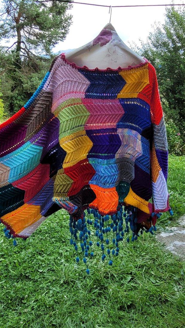 Un pulover  tricotat , colorat, mâneci largi și ciucuri jucăuși